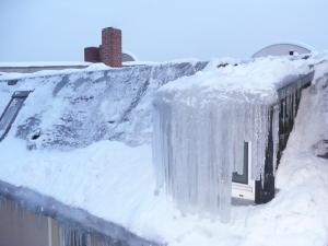 Naturgewalten Eiszapfen vor einer Dachaube